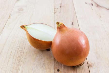 onion slice: Fresh onion bulbs on a wood background. Stock Photo