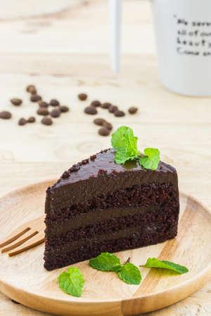 porcion de torta: El chocolate rebanada de la torta en la placa de madera en el fondo de madera.