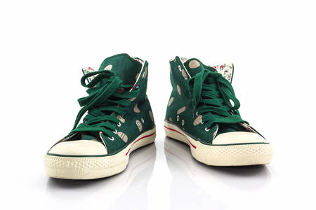 athletic wear: Green polka dot canvas shoe on white background. Stock Photo