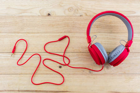 Red Headphones on wood desk Background.