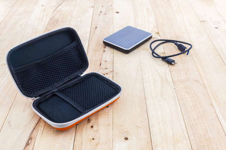 hard drive: External hard drive carrying case. Bags for external hard drive on wood background. Stock Photo