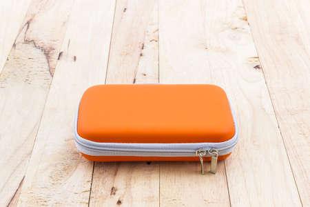 disco duro: Disco duro externo estuche. Bolsas para disco duro externo en un fondo de madera. Foto de archivo