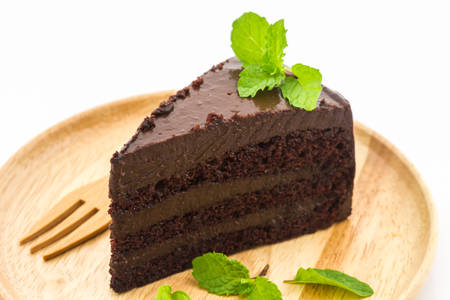 porcion de torta: Torta de la rebanada en la placa de madera sobre fondo blanco. Foto de archivo