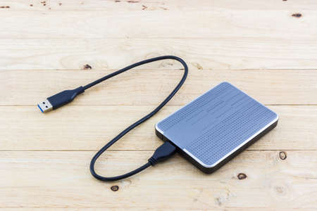External hard drive for backup on wood background. Imagens