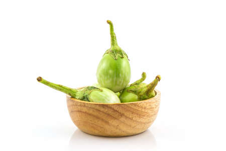 food and nutrition: Thai green eggplant slices in the wood bowl on white background.