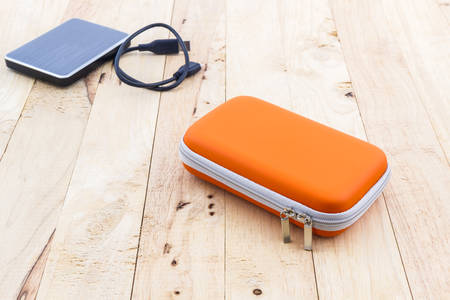 disco duro: External hard drive carrying case. Bags for external hard drive on wood background. Foto de archivo