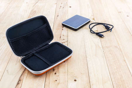 hard drive: External hard drive carrying case. Bags for external hard drive on a wood background.