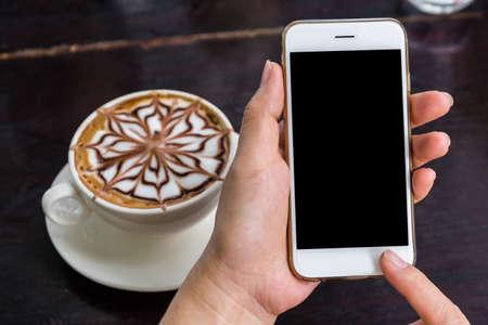 Sluit omhoog van een vrouw gebruikend mobiele slimme telefoon in koffiewinkel.