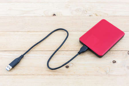 gigabytes: External hard drive for backup on wood background. Stock Photo