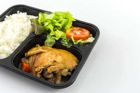 Roasted chicken with rice and vegetable salad in plastic microwavable container on white background.
