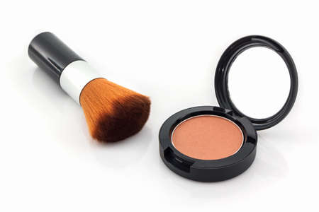 in vain: Closeup of face powder and makeup brush on white background.