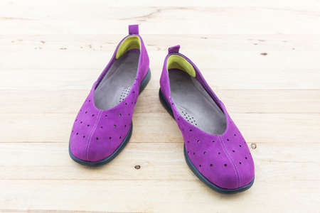 Purple sneakers on a wood background. Canvas Shoe.