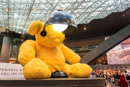 Doha, Qatar - May 4, 2018: The big yellow lamp teddy bear in the middle of the terminal at the Hamad International Airport, Doha, Qatar.