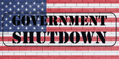 With the word Govermnent Shutdown on flag of united states of america painted over on brick wall.