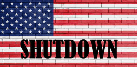 With the word Shutdown on flag of united states of america painted over on brick wall. Reklamní fotografie