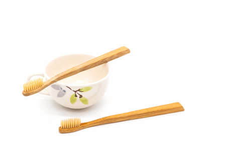 Bamboo toothbrush on ceramic mug on white background.