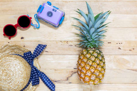 Flat lay pineapple with green leaves and sunglasses, camera, hat on the wooden texture background. Top view.