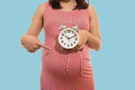gorgeous: Pregnant woman holding  clock. Its time. on blue background soft color