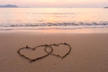 estival: two hearts drawn in beach