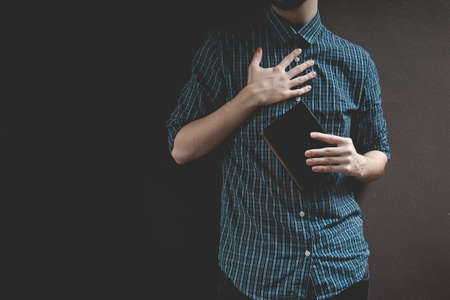Man holding Holy bible. Prayer concept for faith spirituality and religion gray background
