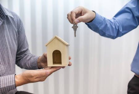 Two real estate brokers hold keys and house models.