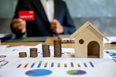 Saving money to buy a house. businessman holding a red credit cardbackground