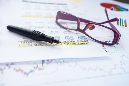business on spreadsheet with pen and eye glass