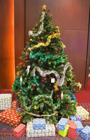 Rotes Zimmer mit Weihnachtsbaum und bunte Geschenk Lizenzfreie Bilder - 24504934