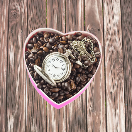Heart shaped coffee in coffee beans with clock