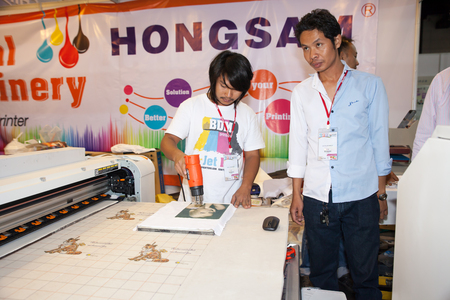 BANGKOK - JUNE 28  Unidentified worker show digital t-shirt printer work with Sewing machine at Garment Manufacturers Sourcing 2014 2014 on June 28,2014 in BITEC ,Bangkok, Thailand