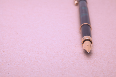 Vintage Fountain Pen on old paper background photo