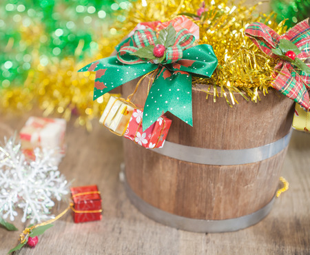 twelve month old: Christmas gift bucket and ribbon over wooden background