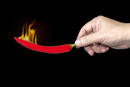 clr: Hand hold fire on hot pepper chilli Stock Photo