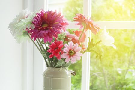 Flowers in glass vase near the window Stock Photo