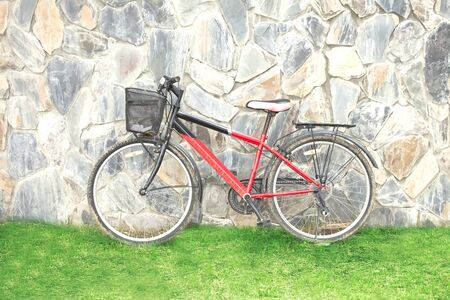 peddle: old red bicycle leaning against a wall