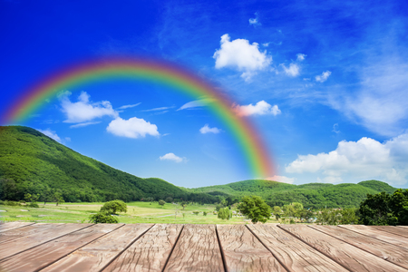rainbow bridge: wood walk with rainbow behind hill Stock Photo