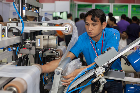 polythene: BANGKOK ,THAILAND - JULY 11: Unidentified people put a plastic roll into machine at InterPlas Thailand 2015 , on JULY 11, 2015 in Bangkok, Thailand. Editorial