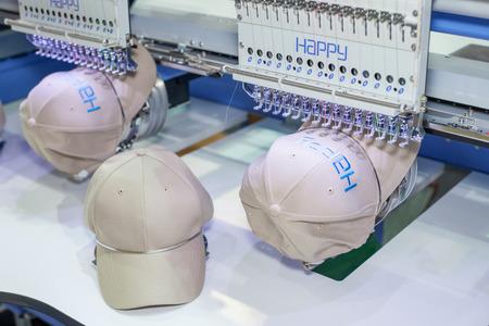 バンコク、タイ - 7 月 11 日: 衣服メーカー調達万博 2015 で (GFT 2015)、2015 年 7 月 11 日、タイのバンコクでの刺繍機でキャップ。