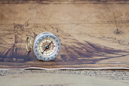 ancient map: Vintage compass lies on an ancient map