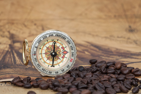 ancient map: Vintage compass and bean lies on an ancient map Stock Photo