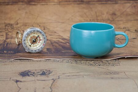ancient map: Vintage compass and cup of coffee lies on an ancient map Stock Photo