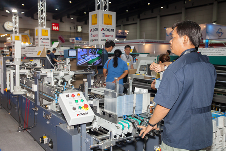 assay: BANGKOK - AUGUST 29 :Unidentified people loading paper to  inspection machine at Pack Print and T-PLAS THAILAND on Aug  29,2015 in BITEC ,Bangkok, Thailand.