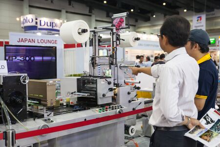 guillotine: BANGKOK - AUGUST 29 :Unidentified people interesting with  plastic coating machine at Pack Print and T-PLAS THAILAND on Aug  29,2015 in BITEC ,Bangkok, Thailand.