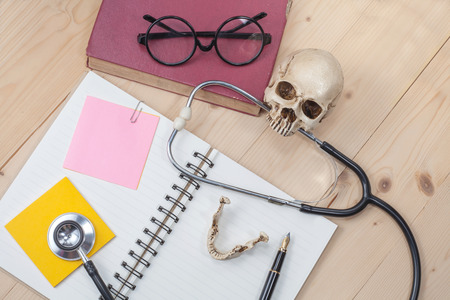 stethoscope , book note and skull on wood