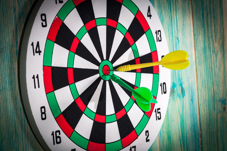 holed: dart board with darts on background