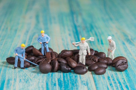 Miniature people working with coffee ,selective focus