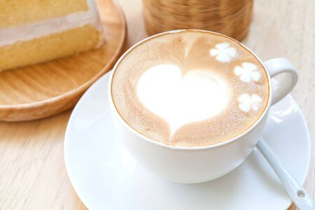 heart symbol on latte coffee cup on table Stock Photo
