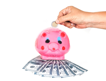 inserting: Inserting a coin into a piggy bank