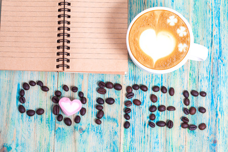 slurp: The word Coffee spelled with coffee beans on wood.