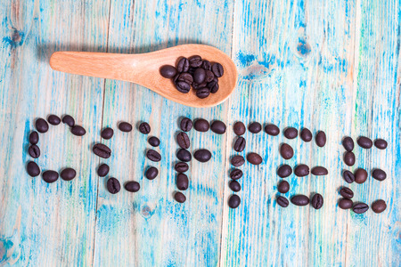 revitalize: The word Coffee spelled with coffee beans on wood.